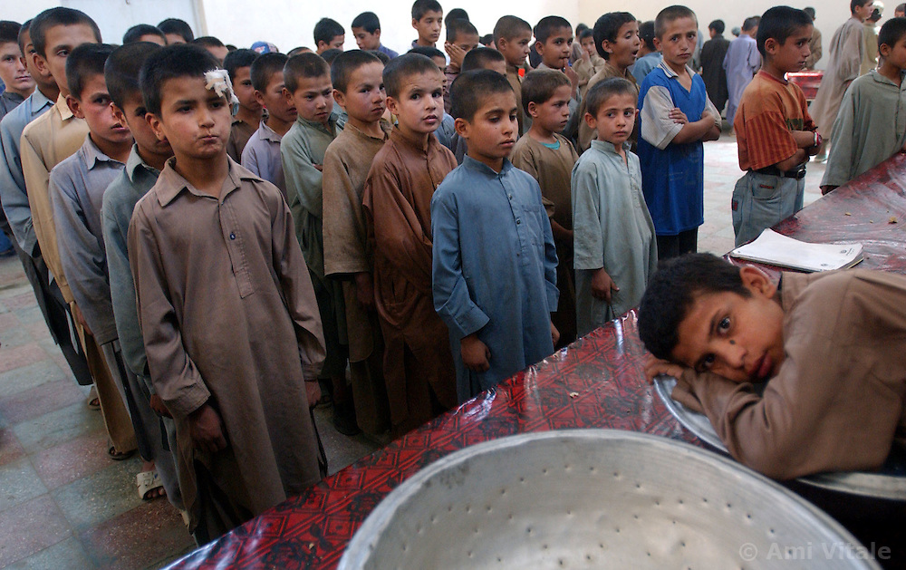 KABUL,AFGHANISTAN - SEPT. 1: Afghan orphans wait in line to eat lunch at an overcrowded orphange in Kabul, Afghanistan September 1, 2002. There are not enough bowls or tables so the 1800 children must wait in line for the next child to finish before they can eat. Despite the huge amounts of foreign aid being brought into the country, many schools and orphanges have seen none of it yet and the alarming rates of child mortality continue to remain among the worst in the world. One in four children die before the age of 5 here.
