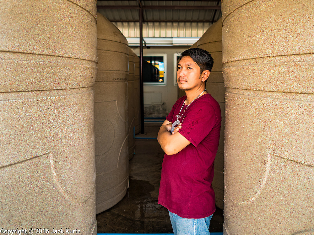 16 MARCH 2016 - PRACHIN BURI, PRACHIN BURI, THAILAND: A worker at Abhaibhubet Hospital in Prachin Buri, stands between water tanks being refilled at the hospital. The drought in Thailand is worsening and has spread to 14 provinces in the agricultural heartland of Thailand. Communities along the Bang Pakong River, which flows into the Gulf of Siam, have been especially hard hit since salt water has intruded into domestic water supplies as far upstream as Prachin Buri, about 100 miles from the mouth of the river at the Gulf of Siam. Water is being trucked to hospitals in the area because they can't use the salty water.        PHOTO BY JACK KURTZ