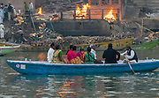 A Hindu family rows down the Ganges past burning wood on funeral pyres next to the Ganges, Varanassi, India