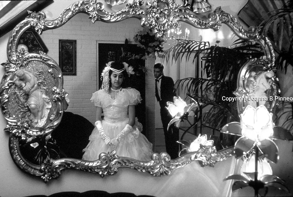 ©2001Joanna B. Pinneo All Rights Reserved.Tucson, Arizona. Maria stands in front of the mirror at her grandparents' home in Tucson just before leaving for her quinceaños celebration. Her 17-year-old brother leans against the wall behind her. Quinceaños is a celebration in the Latin community when a young girl turns 15. It is second only in importance to her wedding. She is the third generation in North America.