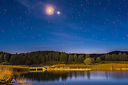 The waxing crescent Moon near Venus on March 22, 2015, over the pond at the Inn of the Mountain Gods, near Ruidoso, New Mexico. The sky was getting quite dark at this point and some light clouds drifted in front of the Moon and Venus, throwing glows around them. <br /> <br /> This is a composite of two exposures: a long 13-second exposure for the main scene and a shorter 3 second exposure for just the Moon and Venus to prevent them from getting too overexposed. Both with the 24mm lens and Canon 60Da.