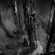 Shaft miners drilling a round in the shaft with jumbo drills, 2500 foot level station, Louvicourt Mine, Val d?Or, Quebec. From the book Cage Call: Life and Death in the Hard Rock Mining Belt. An in-depth project spanning over 12-years examining communities in one of the richest mining regions in the world located in Northwestern Ontario and Northeastern Quebec in Canada.