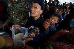Chinese residents receive rations of rice at a distribution point in Yuxi Village of Lushan County, Sichuan Province, China, 23 April 2013. Landslides and fallen rocks block vital roads carrying supplies to remote towns and villages affected by the earthquake. The Lushan Earthquake in Sichuan Province on 20 April 2013 resulted in 186 people dead, 21 missing, 11248 injured. About 1.72 million people were affected by the quake, while an initial estimate by the International Red Cross on Saturday put the number needing emergency shelter, water and food at 120,000. The China Earthquake Administration (CEA) recorded a magnitude 7.0 earthquake, while the US Geological Survey said it had measured 6.9.