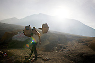 This laborer is returning to the sulfur pits in Ijen, Indonesia.  The workers make up to 20 trips up and down the volcano, each time carrying up to 90kg loads of sulfur.