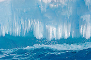 Detail of an iceberg, with icicles over the cold water surface. Portal Point in Antarctica.