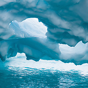 Holes melt in a iceberg overhang which was carved by undercutting waves, in the Southern Ocean offshore from Graham Land, the north part of the Antarctic Peninsula, Antarctica.