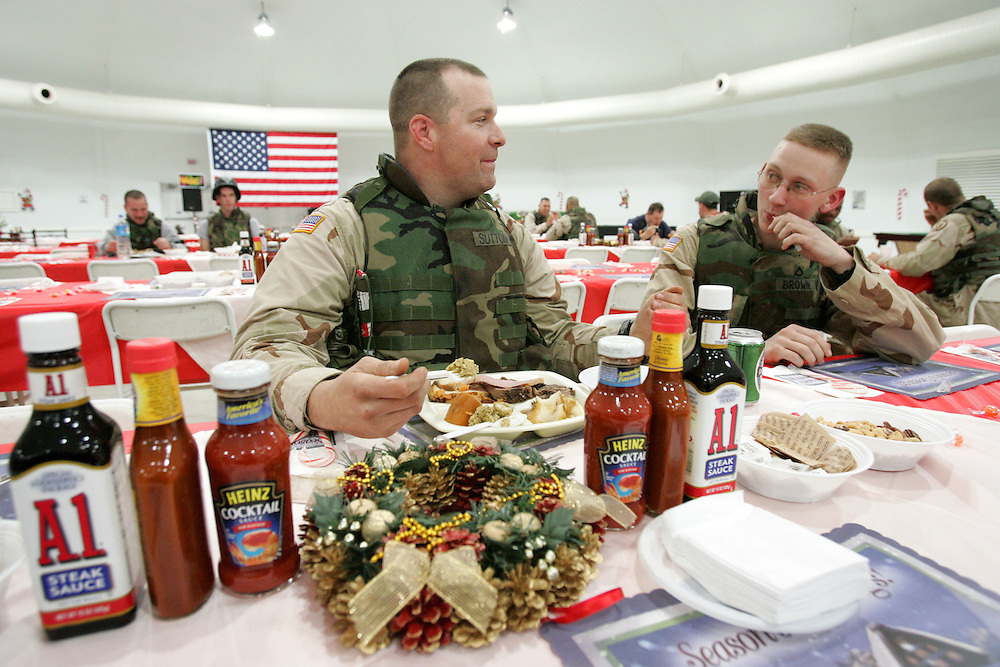 25 December 2004..Mosul, Iraq...Christmas Day/FOB Marez....A suicide bomb attack on the dining facility at Forward Operating Base Marez on the 21 December killed 22 US forces, Iraqis and cillivian contractors. Despite this incident and a ramping up of internal security December 25 saw troops gathering in a hurriedly prepared recreation center for their traditional Christmas lunch. Some units opted to have a take out meal, sending just a few soldiers to collect trays for their fellow troops. Others including some of those those who were in the mess hall on the day of the attack and lost friends chose to sit down and savour their meal. The sentiment expressed was that if the men and women based here allowed such an attack to ruin today then the insurgents had won, the troops took pains to make it clear this was not the case. The meal was served in part by a medic who treated casualties on the 21st and at least one Filipina staff member who was wounded in the explosion.