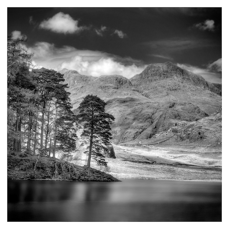 Blea Tarn lies in the Lake District of England.<br /> Dramatically beautiful Blea Tarn, one of the Lake District's innumerable small tarns, occupies a ridge between the Little Langdale Valley and Dungeon Ghyll in Great Langdale. The name blea derives from dark blue.<br /> Set in a superbly panoramic location beneath the shadows of the rugged Langdale Pikes, the tarn stands 700' above sea level. The shores of Blea Tarn are awash with a carpet of wild alpine flowers in the spring and summer.
