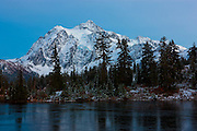 Mount Shuksan, a 9,131 foot (2,783 meter) mountain in Washington's North Cascades, stands tall over the icy Highwood Lake. Mount Shuksan, located in North Cascades National Park, is 9,131 feet (2,783 meters) tall and was formed about 120 million years ago when two of Earth's plates collided and were thrust upward in an event known as the Easton collision.