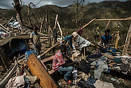LACADONIE, HAITI - OCTOBER 10, 2016:  The Civil family works to clean up and salvage what is left of their home that was destroyed by Hurricane Matthew.  The Civil family joined hundreds of other villagers and lived in a nearby cave for four days and nights, huddled in its womb before emerging, frightened the storm might return. They slept on a floor of stacked boulders near the cave's mouth, lighting small fires for light and warmth.  When they emerged to rebuild their village, they salvaged enough to shield them from the sun, a few corroded sheets of zinc and wooden beams. But when it rains they return to the cave - their shack is unable to keep the water out.  And despite the odor and humidity, the unforgiving crags and its depthless dark, they are thankful.  They now consider the cave a holy place, their only sanctuary left after the storm.