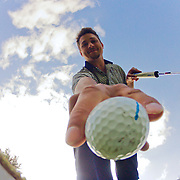 Goldey Beacom college Junior golfer Matthew Japchen .retrieves his golf ball from the hole during a practice session Monday, Apr. 22, 2013 at Deerfield Country Club in Newark Delaware..