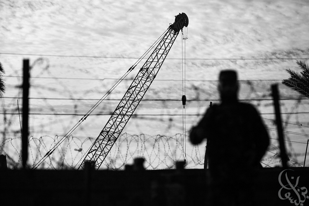 A Palestinian border guard watches as Egyptian heavy equipment works on a mysterious anti-smuggling tunnel project on the Egyptian-Gaza border December 21,2009 at Rafah. Egyptian authorities have not disclosed any details of the project, which is alternately rumored to be a 20 meter deep underground wall, a water saturation mechanism, or a combination of both. Whatever the reality of the project, HAMAS and the Gaza smugglers who rely on the tunnels to bring in everything from fuel to food to weapons are nervous about the prospects.