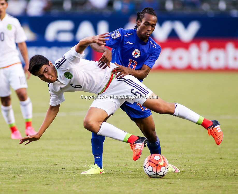 Mexico midfielder Eric Gabriel Gutiérrez Galaviz, front, and Haiti midfielder Venel Saint Fort #13 flight for a ball in the second half of a CONCACAF men's Olympic qualifying soccer match in Carson, Calif., Sunday, Oct. 4, 2015. Mexico won 1-0. (AP Photo/Ringo H.W. Chiu)