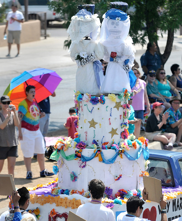 mkb062913e/metro/Marla Brose/062813<br /> A wedding cake with two brides rolls down Central Ave. during the 2013 Albuquerque Pride Parade 2013, Saturday, June 29, 2013, in Albuquerque, N.M. The side of the float reads, &quot;Why Marriage Matters NM&quot;.(Marla Brose/Albuquerque Journal)
