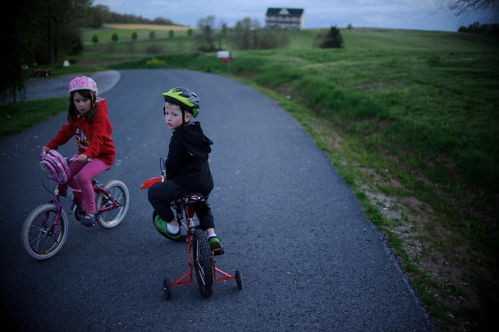 photo by Matt Roth.Wednesday, April 11, 2012..Rory and Miles ride bikes at dusk Wednesday, April 11, 2012. Ron Shriver likes his children to play before bed so they're more likely to go to sleep. ..Ron Shriver grew up on a large farm house in Pleasant Valley, Maryland, a small township outside Westminster. After his lease was up, he moved back to his parent's home with his two children Rory and Miles, living temporarily in their basement before graduating from McDaniel College in May. After tossing his graduation cap, he and his children will drive cross country to meet up with his wife who has been working on her graduate degree in Alaska. ..Ron Shriver is a retired marine staff sergeant. He is also the first in his family to attend college, thanks to the New G.I. Bill. His wife, a fellow retired Marine, is finishing up graduate school in Alaska. After Ron gets his undergraduate degree from McDaniel College in May, he plans to drive to Alaska with is two children Rory, 6, and Miles, 5. For the move Ron got rid of most of his family's belongings, and after his lease was up, he and his children moved back into his parent's farmhouse.