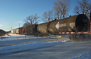 Ames,Iowa,USA Snowy and cold,crisp and clear with blue sky, tank cars passing guard rail