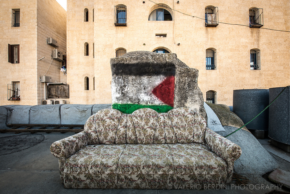 A sofa and a painted Palestinian flag on a desolate roof terrace of a house adjacent to a modern building, seen on the back, occupied by Israeli settlers. While Palestinians hardly get permissions to extend or build new houses, Israel support the illegal occupation of the settlements. in 2007 Abed Seder's wife, Kefah, was shot five times in the chest by Israeli soldiers as she went onto this roof to check her water tank. She was 23 years old and left three sons motherless. He tells me his sons are afraid to go on the roof, which overlooks the illegal Zionist settlement of Beit Hadassah.