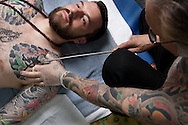 Horiyoshi III (the 3rd) (right of pic), expert Japanese tattooist, adds colour to a tattoo on the forearm of his German understudy Alex Reinke (also known as Horikitsune) (left of pic), in Horiyoshi's studio in Yokohama, Japan, on Saturday 10th September 2011.