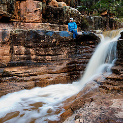 Melanie Van Dorp relaxes next to a seasonal waterfall in the mountains of northwestern New Mexico.