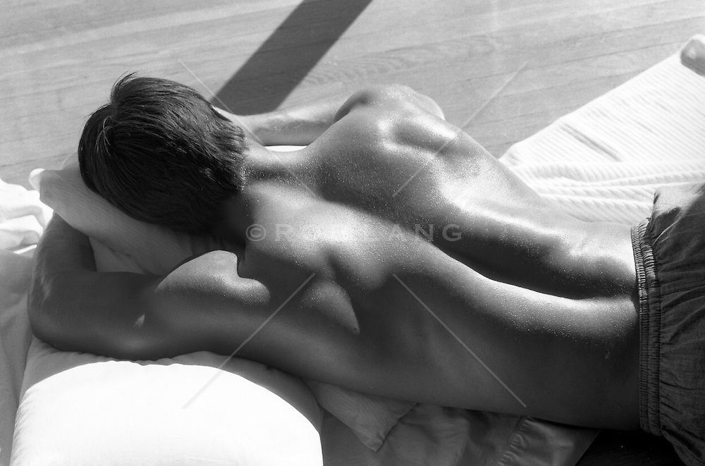 Back of shirtless young man asleep on his bed holding his pillow