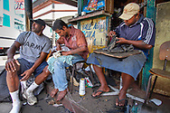 Suva, Fiji: Roneel Chand (center) repairs shoes at a stall in downtown Suva, while his family grows cash crops on leased land in nearby Navua.