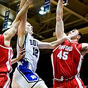 21 November 2009: Duke Junior Forward #12 Kyle Singler drives hard to the basket aginst Radford (45) Artsiom Parakhouski senior center..Duke Rolls Past Radford 104-67 .Mandatory Credit: Mark Abbott / Southcreek Global