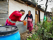 01 MARCH 2017 - KHOKANA, NEPAL: A woman washes her face next to her temporary shelter, provided by a NGO after the 2015 earthquake. She's been living in the shelter with her family for nearly two years. Recovery seems to have barely begun nearly two years after the earthquake of 25 April 2015 that devastated Nepal. In some villages in the Kathmandu valley workers are working by hand to remove ruble and dig out destroyed buildings. About 9,000 people were killed and another 22,000 injured by the earthquake. The epicenter of the earthquake was east of the Gorka district.     PHOTO BY JACK KURTZ