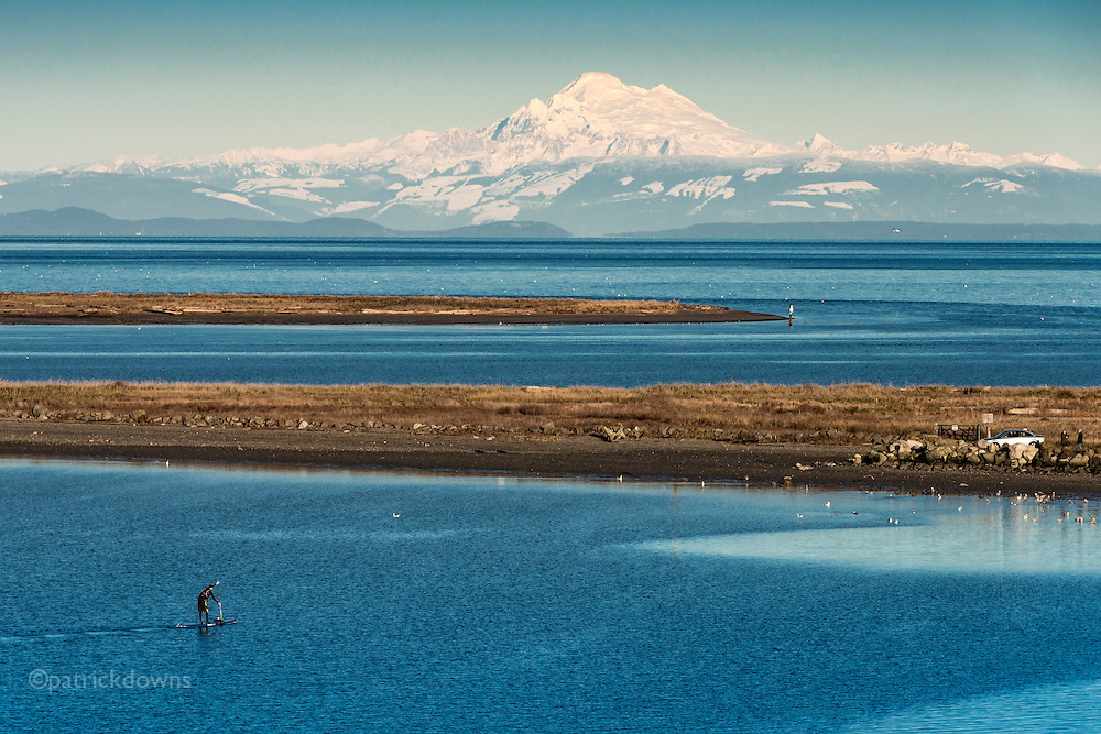 A SUP paddleboarder heads in to shore at Cline Spit in Sequim, WA on a cold day. Mt. Baker can be seen in the distance.
