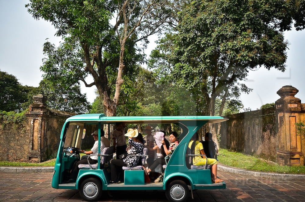 A green minibus for tourists is carrying a group of dozen Vietnamese tourists in the Hue citadel. Vietnam, Asia