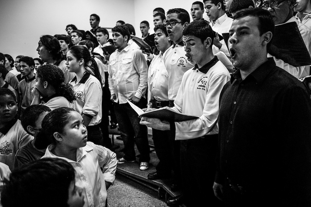 Members of a youth choir watch in admiration as an older, advanced choir performs for guests at the El Sistema nucleo in Maracay, Venezuela.