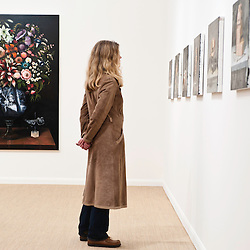 London, UK - 11 October 2012: a visitor looks up at paintings during the Frieze Art Fair 2012, London's big annual art fair that takes place in Regent's Park. It sells the works by more than 1,000 of the world's leading artists, represented by some 170 international galleries.