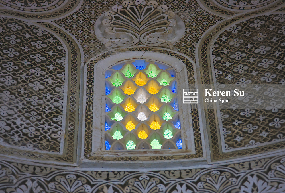 Architectural details, window with stained glass and plaster made intricate pattern inside dome house, Kairouan, UNESCO World Heritage site, Tunisia