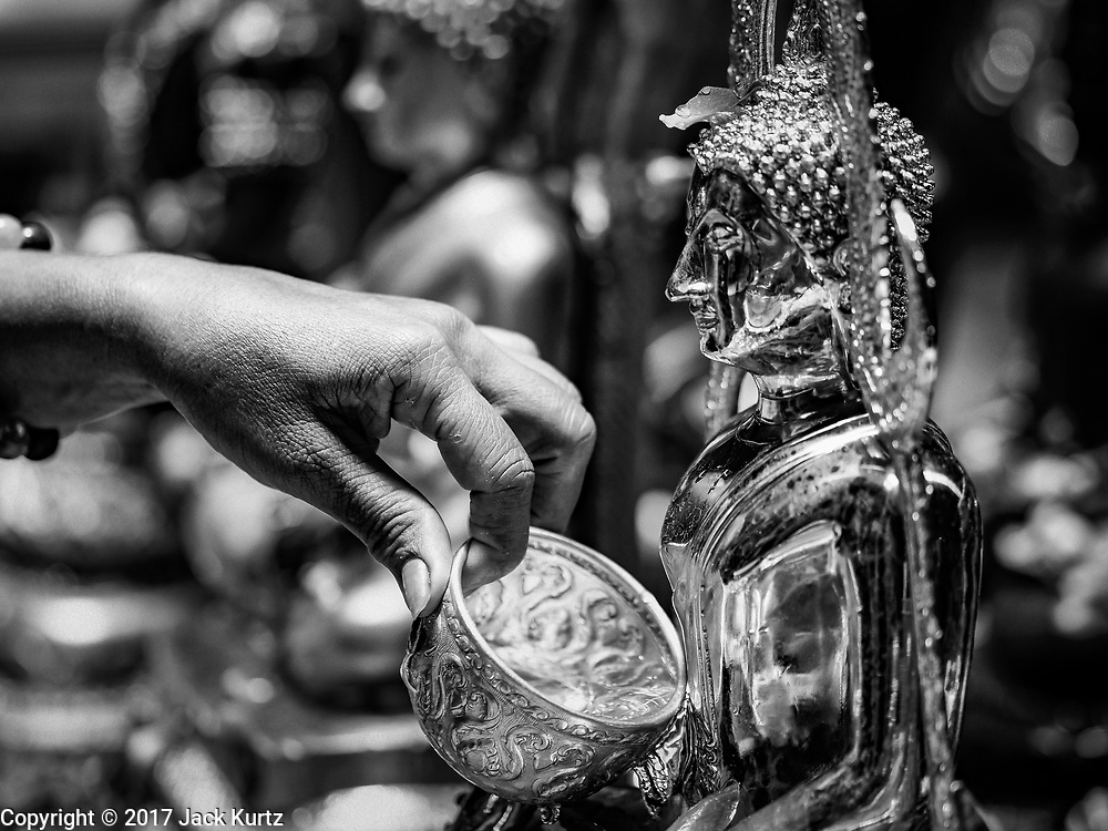 """11 APRIL 2017 - BANGKOK, THAILAND: A woman bathes a statue of the Buddha in scented water during the Songkran travel period at Hua Lamphong train station in Bangkok. Songkran is the traditional Thai Lunar New Year. It is celebrated, under different names, in Thailand, Myanmar, Laos, Cambodia and some parts of Vietnam and China. In most places the holiday is marked by water throwing and water fights and it is sometimes called the """"water festival."""" This year's Songkran celebration in Thailand will be more subdued than usual because Thais are still mourning the October 2016 death of their revered Late King, Bhumibol Adulyadej. Songkran is officially a three day holiday, April 13-15, but is frequently celebrated for a full week. Thais start traveling back to their home provinces over the weekend; busses and trains going out of town have been packed.     PHOTO BY JACK KURTZ"""