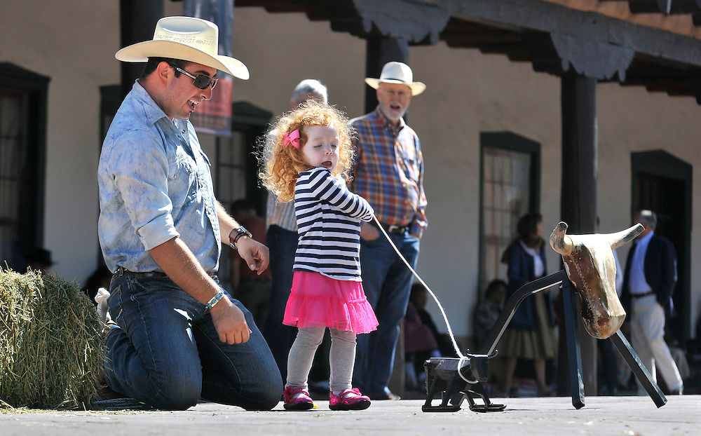 em081013a/jnorth/daily/Reynaldo Maestas, from Rociada, N.M., helps Charlotte Greenhaw, 3, from Oklahoma City, rope a small toy steer in front of the Palace of the Governor's, in Santa Fe, Saturday August 10, 2013. Maestas and his brother Julio were giving roping demonstrations as part of the Wild West Weedend put on by the New Mexico History Museum in the Palace of the Governor's Courtyard. (Eddie Moore/Albuquerque Journal)