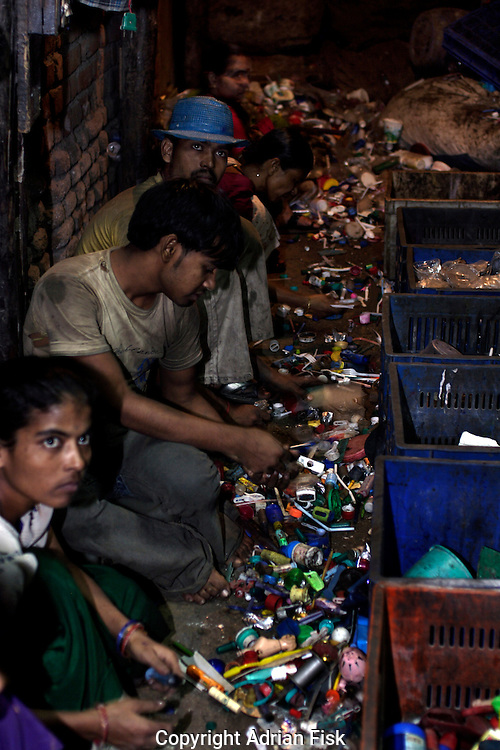 Workers sort plastic by colour. Dharavi is the centre of Bombays recycling industry and is particularly well known for plastic recycling. Plastic is sorted by colour then ground up into small pieces and dyed. It is then melted and moulded into plastic sheets ready to be sold on..labourers get the standard Dharavi rate of Rs80 ($1.80) for a 12 - 14 hour day, once finished they clear a space and cook and sleep in the same room.