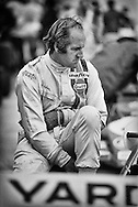1967 Formula One World Champion, Denny Hulme takes a moment to gather his thoughts before qualifications begin for the 1972 United States Grand Prix at Watkins Glen. He always seemed his quickest when he was at peace. It was the end of a long 1972 season that saw New Zealand's Hulme's McLaren again finish 3rd in the World Championship. <br /> <br /> Hulme had also raced for McLaren in the Can-Am series that year with teammate and great friend Peter Revson, where they had to give up their three-year domination of the championship to the new Team Penske Porsche 917/10. Hulme lamented that Formula One had begun to change with the advent of large sponsorships, marketing demands, and huge budgets manipulating &quot;pure racing&quot;.<br /> <br /> Hulme began his racing career in junior formula classes in Europe before becoming a mechanic for Australian Jack Brabham's F1 team. By 1966, he had convinced Brabham he would be a great teammate and by 1967, he had contested and won the Formula One World Championship over Brabham by five points. <br /> <br /> He moved to fellow Kiwi Bruce McLaren's team in 1968, where he finished 3rd in the standings. When McLaren was killed in 1970, he became team leader, inheriting a team that was in disarray.<br /> <br /> Peter Revson joined Hulme on the McLaren F1 team for 1972-73, but sponsor Marlboro insisted that Emerson Fittipaldi replace Revson in 1974.<br /> <br /> When Revson was killed testing for UOP Shadow that same year in South Africa, Hulme lost his last strings to Formula One  and retired at the end of the season, returning to the peace of New Zealand.<br /> <br /> He never lost his passion for &quot;pure racing&quot; though and competed in many national motor sport events. He died of a massive heart attack while racing a BMW M3 in the 1992 Bathhurst 1000 at Mount Panorama, Australia.