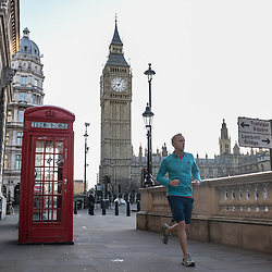 London, UK - 25 December 2014: a young man runs past one of the most photographed telephone booths on early Christmas morning