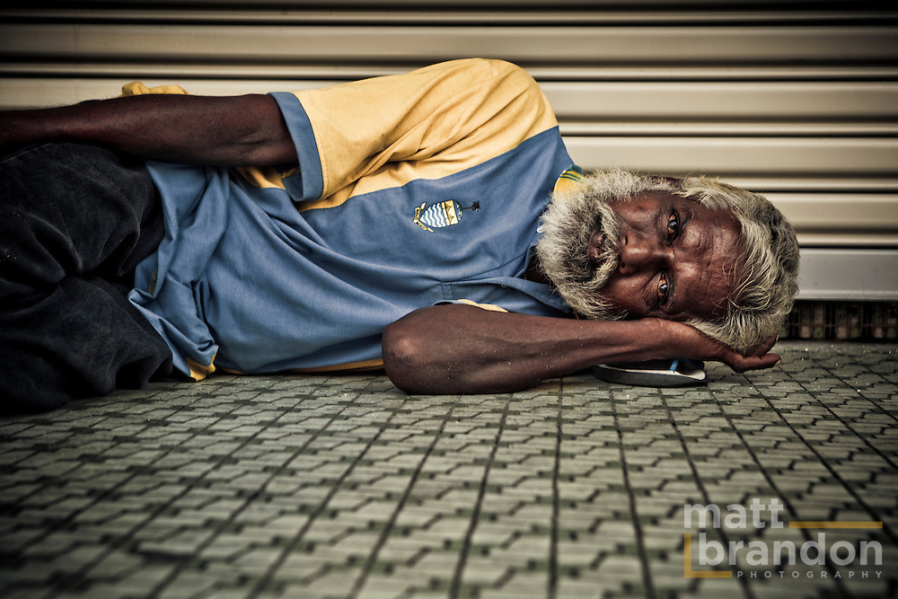 A homeless man rests in downtown  Georgetown. He uses his rubber flip-flop sandal of the pillow.
