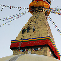 Three Tibetans climb high up on the Boudhanath Stupa in Kathmandu to clean it.  A very important pilgrimage site, it was said to have been built in the 5th century C.E.