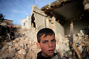 A boy stand in front of totally destroyed hoouse after an assault by syrian army. On 22. February the syrian army attacked the village of Kureen, Province of Idlib, Syria. Kureen was among the first villages in the northwest of Syria controlled by the opposition. Some villagers and members of the defence units escaped to surrounding olive orchards, when the attack begun in the early morning. A majority of the inhabitants didn´t manage to escape. The heavy shelling lasts 7 houres. Soldiers searched all houses, burnt some of them down, loote shops, stole cars and furniture. About 60 motorcycles were burnt down. Tanks demolished several houses. 6 men were executed. One woman died as a result of an heart attack.
