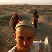 Local Afghani children wander around a vast cemetery near the front lines in Khoja Bahauddin.