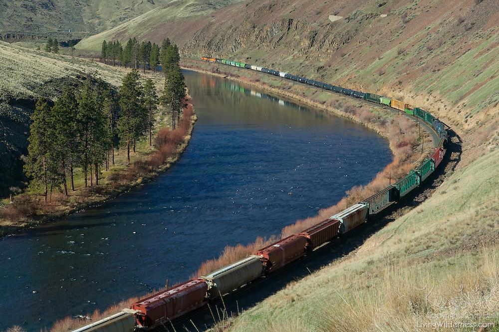 A long Burlington Northern-Sante Fe train is partially reflected in the Yakima River near Yakima, Washington.