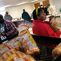 LEHIGH ACRES, FL -- January 23, 2009 -- Marjorie Atkinson, right, and her husband, Cyrus, who are facing foreclosure on their home, search for free bread at the bread line at Faith Lutheran Church in Lehigh Acres, Fla., on Friday, January 23, 2009.  Lehigh Acres has become a symbol for the fallen American Dream - with only two years separating itself from housing market boomtown to a current landscape of abandoned developments and struggling businesses.