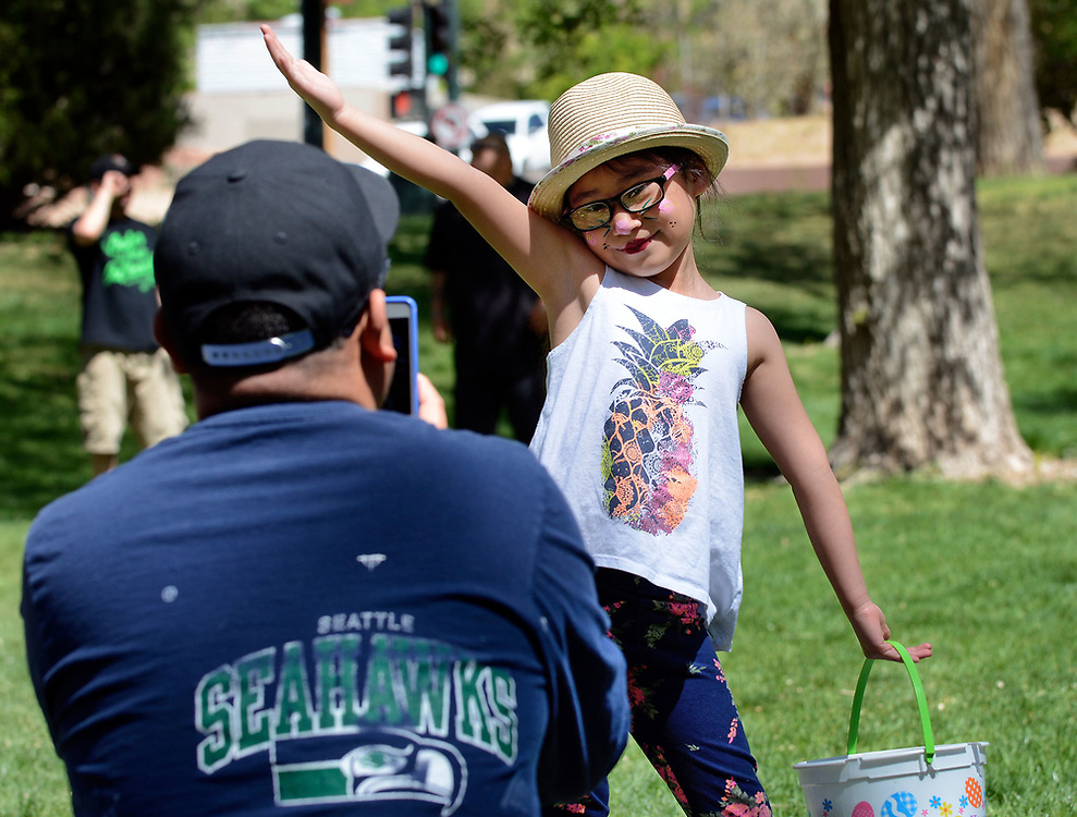 jt041517d/a sec/jim thompson/ Florenzia Resendiz strikes a pose for her father Oscar as he takes her picture at the Victory Outreach Albuquerque Church's HOPE Easter Egg Hunt and care Basket Giveaway at Roosevelt Park.  Saturday April 15, 2017. (Jim Thompson/Albuquerque Journal)