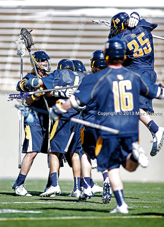 SHOT 3/2/13 1:47:55 PM - Marquette lacrosse players hug at midfield after beating Air Force in their college lacrosse game at Falcon Stadium in Colorado Springs, Co. Marquette won the game 8-6 marking their first ever win as a new program. (Photo by Marc Piscotty / © 2013)