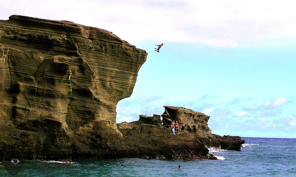 A gutsy individual jumps from atop the rocky cliffs about the Green Sand Beach on the Big Island of Hawaii as other watch from below. The beach lies at the base of Pu'u o Mahana, a cinder cone formed during an early eruption of Mauna Loa; the greenish tint is caused by an accumulation of olivine that forms in volcanic eruptions.