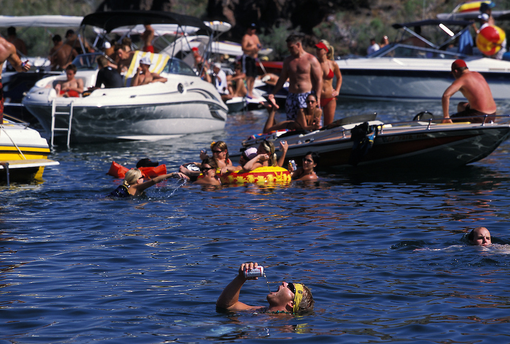 "Scott Chamber, in water drinking beer, parties on Lake Havasu during Memorial Day weekend. Each year there are several incidents of ""prop chop"" where people in the water are injured by boat props."