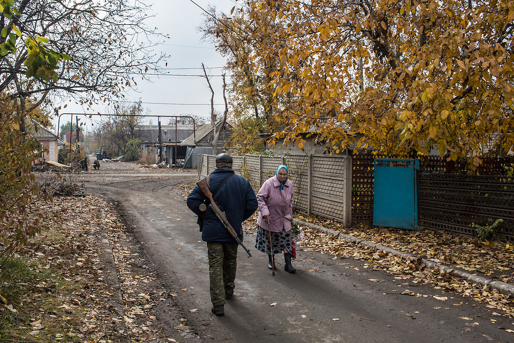 Nadezda Panasyk, 75, walks past a pro-Russian rebel in the Kievsky district where she lives on Friday, October 17, 2014 in Donetsk, Ukraine. Her apartment building is used by fighters for the Donetsk People's Republic to coordinate efforts to gain control of the Donetsk airport, one of the most heavily contested ongoing battles of the war in Eastern Ukraine. Photo by Brendan Hoffman, Freelance