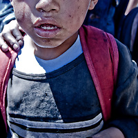 a tear stains the face of a young boy in Ecuador as he begs for money, his hands blackened from shining shoes