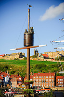 Crows nest statue on Whitby harbour with the abby on the hill behind
